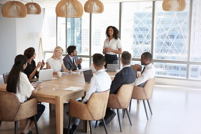 Η επιχειρηματίας στέκεται να απευθυνθεί στη συνεδρίαση γύρω από τον πίνακα πινάκων στοκ φωτογραφία
