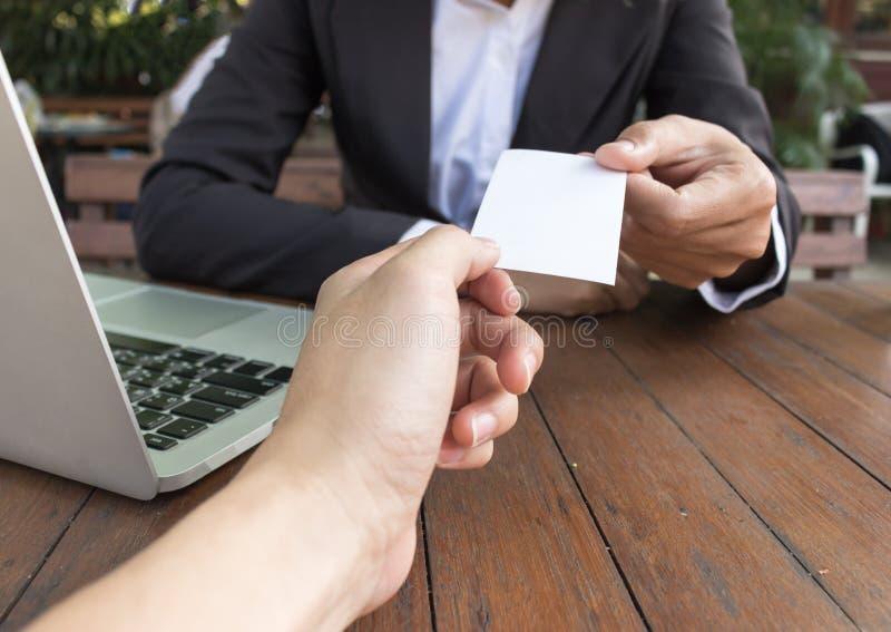 Η επιχειρησιακή γυναίκα δίνει τη επαγγελματική κάρτα για τον πελάτη στη καφετερία στοκ φωτογραφία