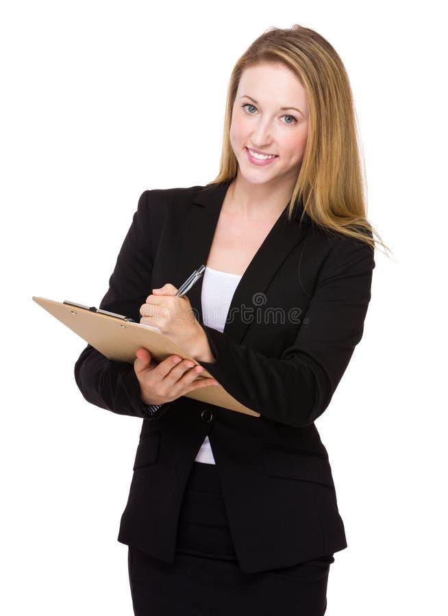 Η επιχειρησιακή γυναίκα γράφει στην περιοχή αποκομμάτων στοκ φωτογραφία