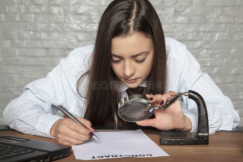 Η επιχειρησιακή γυναίκα διαβάζει τη σύμβαση πολύ προσεκτικά στοκ εικόνα