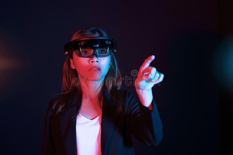 Η επιχειρησιακή γυναίκα δοκιμάζει vr τα γυαλιά hololens στο σκοτεινό δωμάτιο | Πορτρέτο της νέας ασιατικής εμπειρίας AR κοριτσιών στοκ εικόνες