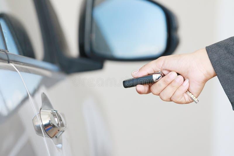 Η επιχειρησιακή γυναίκα ενεργοποιεί το μακρινό βασικό αυτοκίνητο στοκ εικόνες