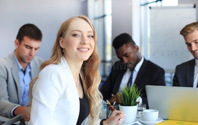 Η επιχειρησιακή γυναίκα με το προσωπικό της, άνθρωποι ομαδοποιεί στο υπόβαθρο στο σύγχρονο φωτεινό γραφείο στο εσωτερικό στοκ εικόνα με δικαίωμα ελεύθερης χρήσης