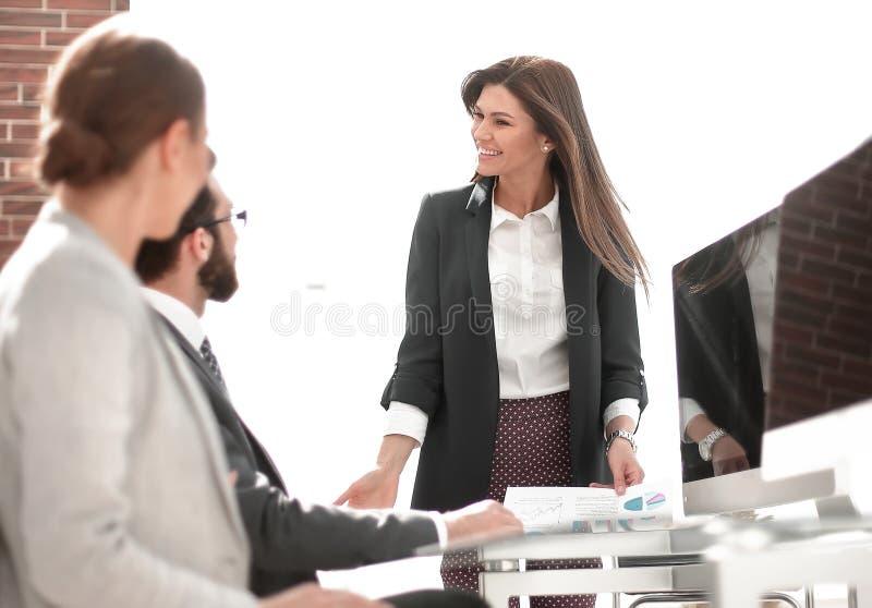 Η επιχειρησιακή γυναίκα πραγματοποιεί μια εργαζόμενη συνεδρίαση στο γραφείο στοκ εικόνα