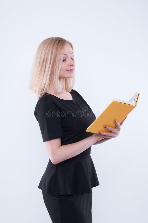 Η επιχειρησιακή γυναίκα στο μαύρο φόρεμα κρατά το κίτρινο βιβλίο στα χέρια και το κοίταγμα στο βιβλίο στοκ φωτογραφίες με δικαίωμα ελεύθερης χρήσης