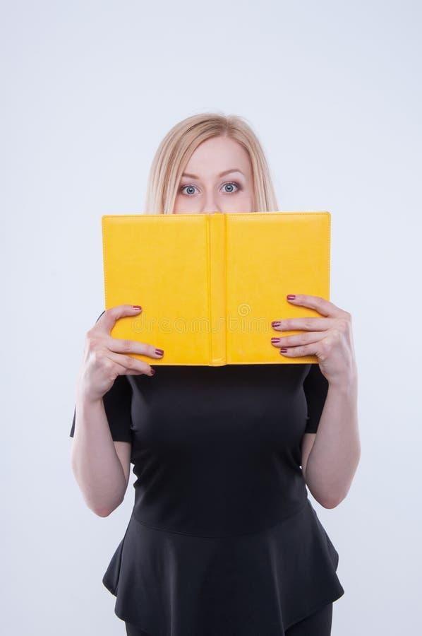 Η επιχειρησιακή γυναίκα στο μαύρο φόρεμα κρατά το κίτρινο βιβλίο στα χέρια και το κοίταγμα στο βιβλίο στοκ φωτογραφία με δικαίωμα ελεύθερης χρήσης