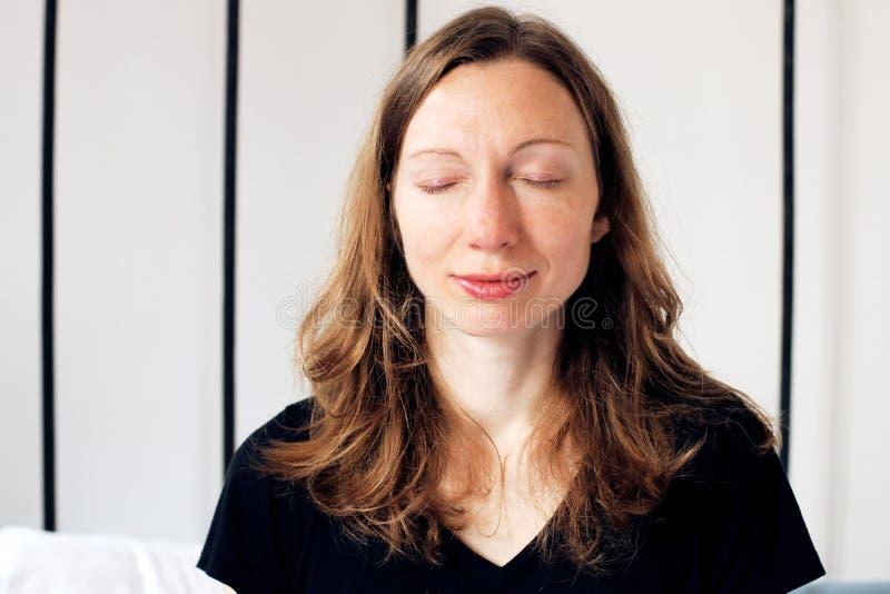 Η επιχειρησιακή γυναίκα της Zen που κάνει τις ασκήσεις αναπνοής στο κρεβάτι που χαλαρώνουν στο λωτό θέτει στοκ εικόνα