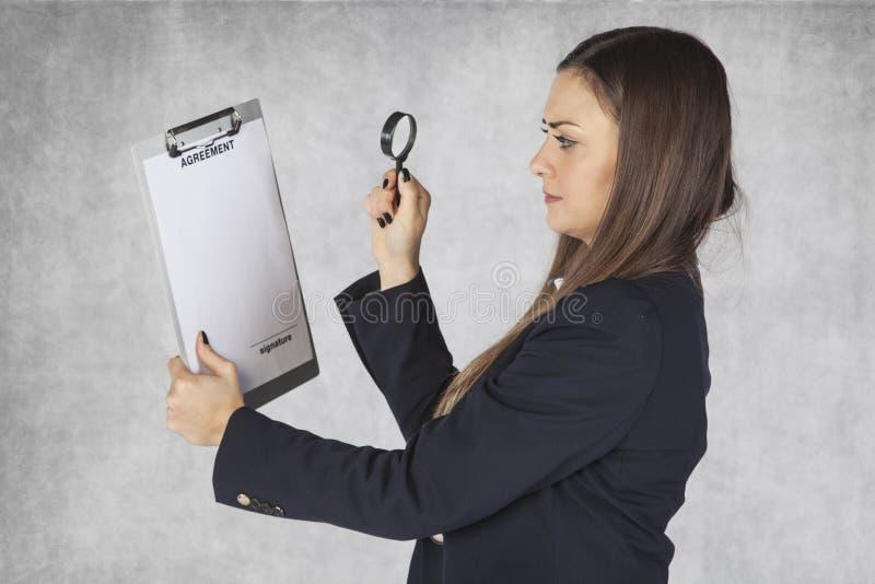 Η επιχειρησιακή γυναίκα χρησιμοποιεί μια ενίσχυση - γυαλί για να διαβάσει τη συμφωνία στοκ εικόνες με δικαίωμα ελεύθερης χρήσης