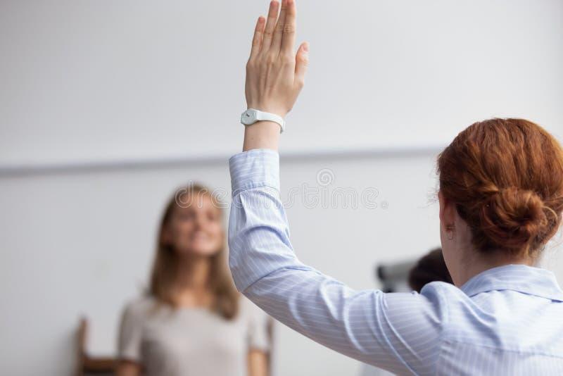 Η επιχειρησιακή κυρία αυξάνει το χέρι ψηφίζοντας κατά τη διάρκεια της επιχειρησιακής συνεδρίασης στοκ εικόνα