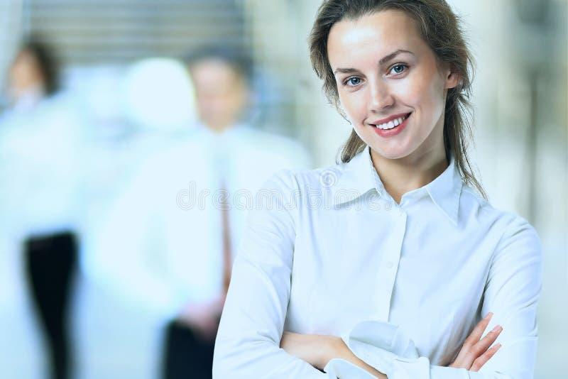Η επιχειρησιακή κυρία με το θετικό κοιτάζει και εύθυμη τοποθέτηση χαμόγελου στοκ εικόνες