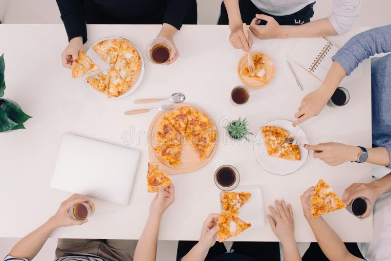 Η επιχειρησιακή ομάδα τρώει την πίτσα στην εργασία εργαζόμενη στοκ εικόνες
