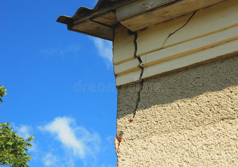 Η λεπτομέρεια αρχιτεκτονικής της χαλασμένης γωνίας σπιτιών κατέστρεψε τον παλαιό τοίχο προσόψεων οικοδόμησης πέρα από το υπόβαθρο στοκ φωτογραφία
