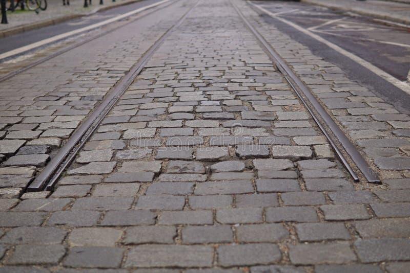 Η λεπτομέρεια ενός τέλους των σιδηροδρομικών γραμμών μεταξύ ο δρόμος ως σύμβολο του τελικού σταθμού στοκ εικόνες