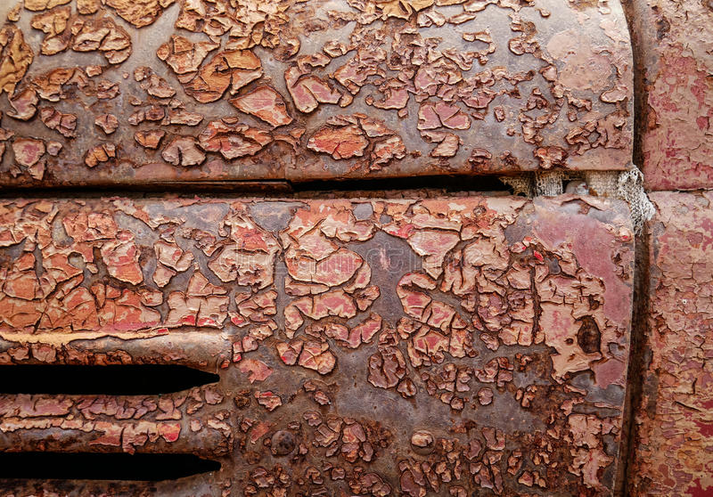 Η λεπτομέρεια και κλείνει επάνω της σκουριάς στο μέταλλο αυτοκινήτων με το ράγισμα, την παρουσία σκουριάς και τη διάβρωση, όμορφο στοκ εικόνα
