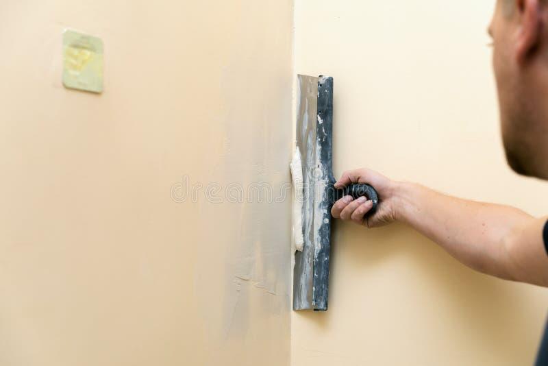 Η εργασία ευθυγραμμίζει - τοίχος επικονίασης εργαζομένων με spatula στοκ εικόνες με δικαίωμα ελεύθερης χρήσης
