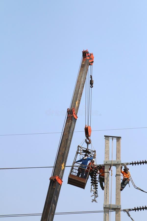 Η εργασία ηλεκτρολόγων στο ύψος συνδέει κοντά ένα καλώδιο υψηλής τάσης στοκ φωτογραφία με δικαίωμα ελεύθερης χρήσης
