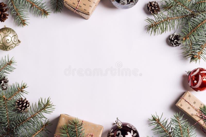 Η ερυθρελάτη σφαιρών κώνων πεύκων κιβωτίων δώρων σύνθεσης διακοσμήσεων Χριστουγέννων διακλαδίζεται στον άσπρο εορταστικό πίνακα στοκ φωτογραφία με δικαίωμα ελεύθερης χρήσης
