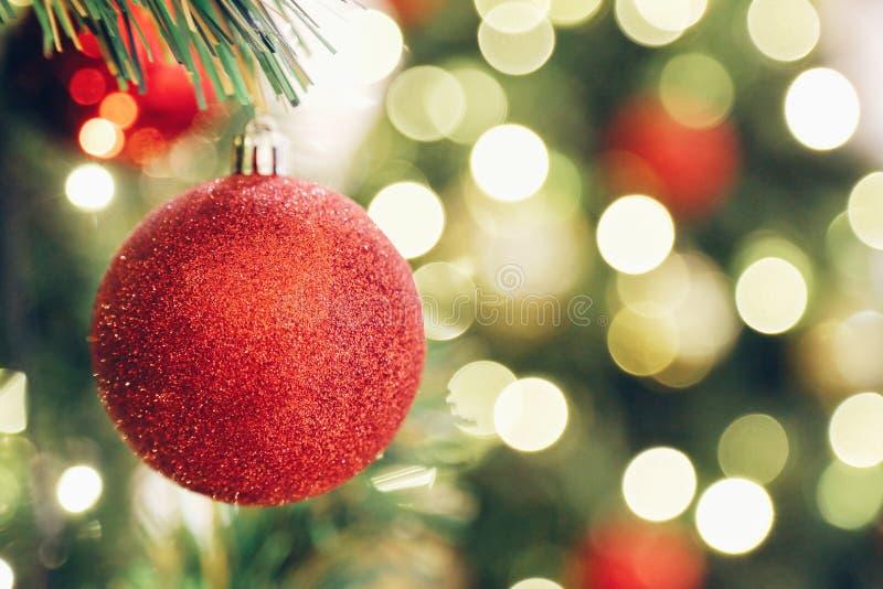 Η εστίαση που λαμπιρίζει ακτινοβολεί κόκκινη σφαίρα στο χριστουγεννιάτικο δέντρο και το φως θαμπάδων bokeh στο υπόβαθρο στοκ εικόνες
