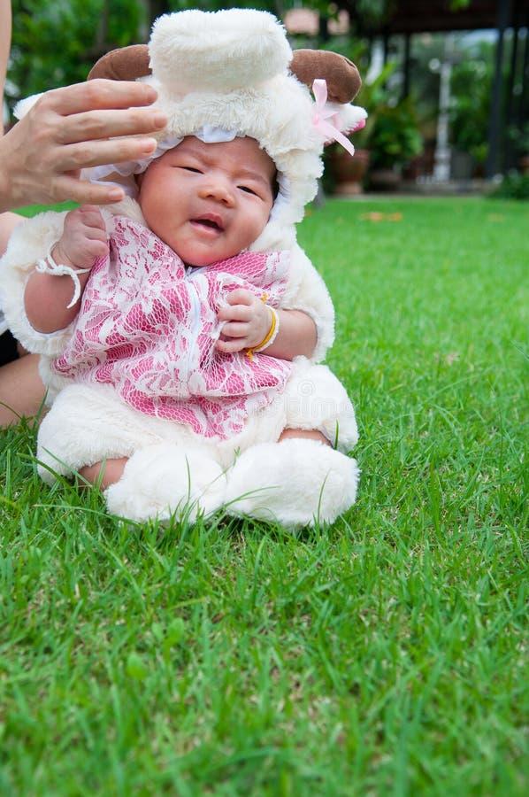 Η εστίαση στο ασιατικό νεογέννητο κοριτσάκι με τα κοστούμια λίγο πρόβατο στον κήπο και τη μητέρα την κρατά στοκ φωτογραφία