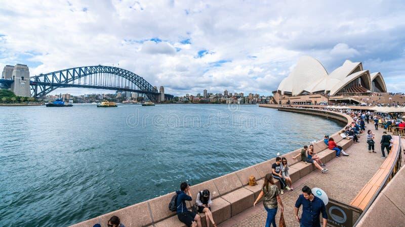 Η ευρεία άποψη γωνίας του περιπάτου που οδηγεί στη Όπερα του Σίδνεϊ με τους ανθρώπους και το λιμάνι γεφυρώνουν στο Σίδνεϊ NSW Αυσ στοκ εικόνες
