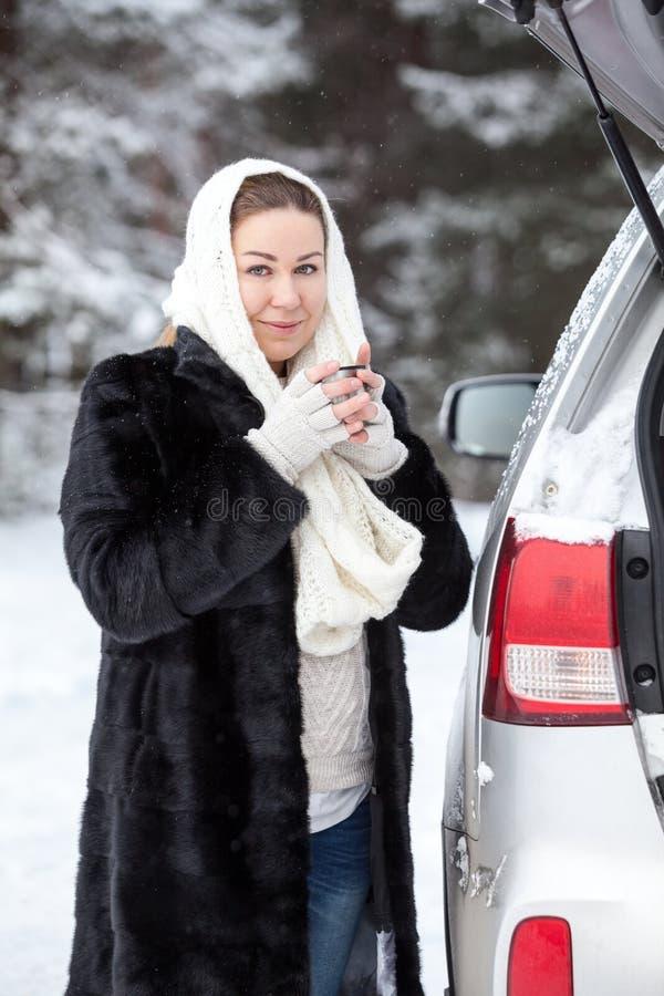 Η Ευρωπαία γυναίκα με το θερμό ιματισμό παγώνει στο χειμερινό δασικό κοντινό σπασμένο αυτοκίνητο, πίνοντας το καυτό ποτό στοκ εικόνες