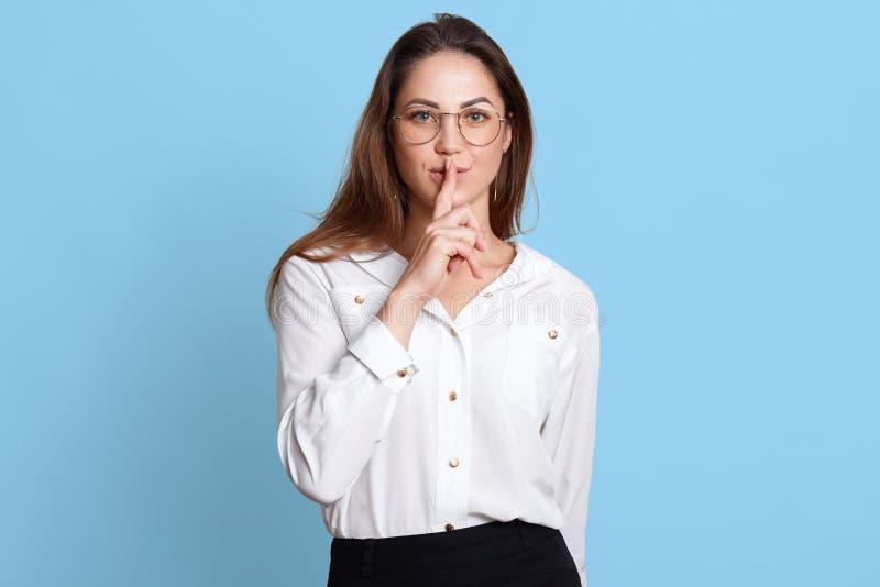 Η Ευρωπαία λεπτή γυναίκα παρουσιάζει με τη χειρονομία για να κρατήσει στη σιωπή, που κρατά το δείκτη κοντά στα χείλια, στάσεις στ στοκ εικόνες