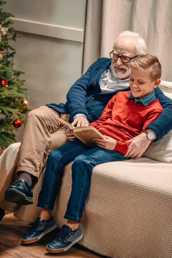 η ευτυχής ανάγνωση παππούδων και εγγονών κρατά στα Χριστούγεννα καθμένος στοκ εικόνα