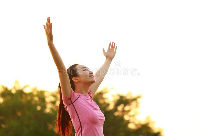 Η ευτυχής ασιατική κινεζική γυναίκα αγκαλιάζει τη φύση και τον ήλιο στοκ εικόνα