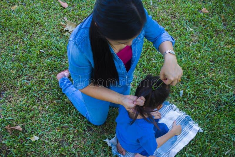 Η ευτυχής ασιατική μητέρα δένει την τρίχα του ήλιού της ενώ η λατρευτή αρσενική κατανάλωση παιδιών τσιμπά στοκ φωτογραφία