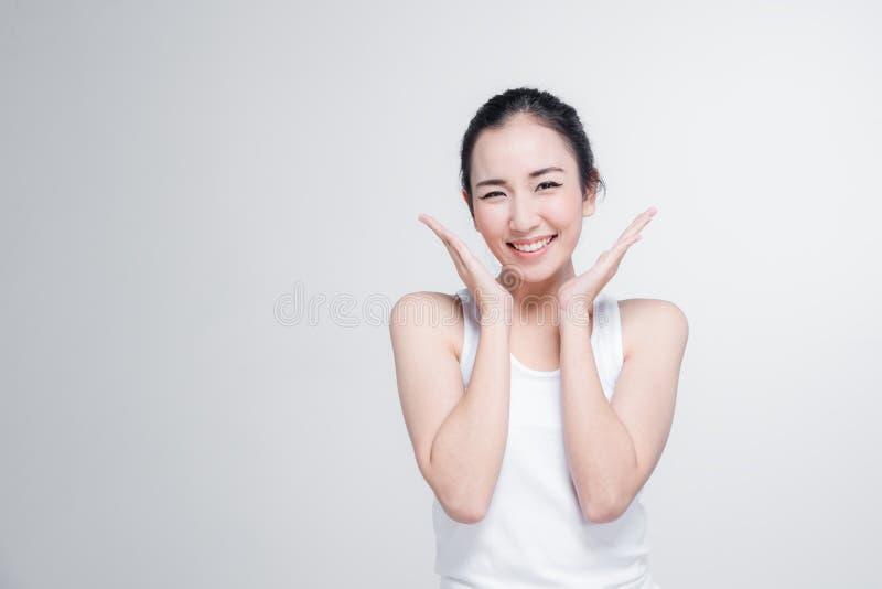 Η ευτυχής ασιατική νέα γυναίκα όμορφη με σκέφτεται τη στάση χειρονομίας στο άσπρο υπόβαθρο στοκ εικόνες