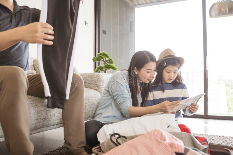 Η ευτυχής ασιατική οικογένεια προετοιμάζεται για το ταξίδι στο σπίτι Η κόρη και ο πατέρας Mom συσκευάζουν τις βαλίτσες για το ταξ στοκ εικόνες