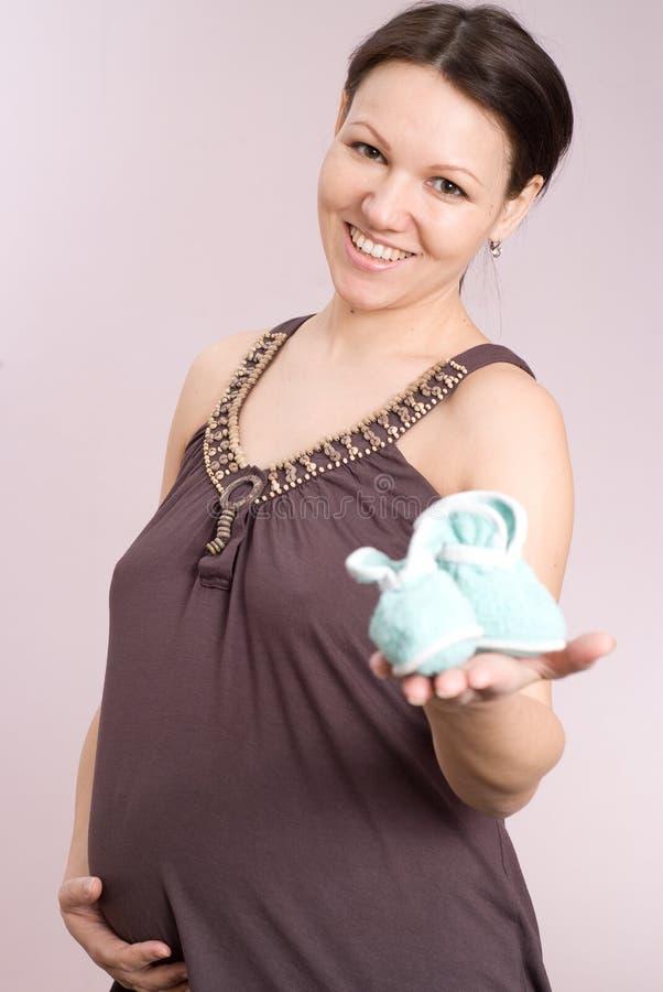 Η ευτυχής γυναίκα εμφανίζει ενδύματα των παιδιών στοκ εικόνα με δικαίωμα ελεύθερης χρήσης