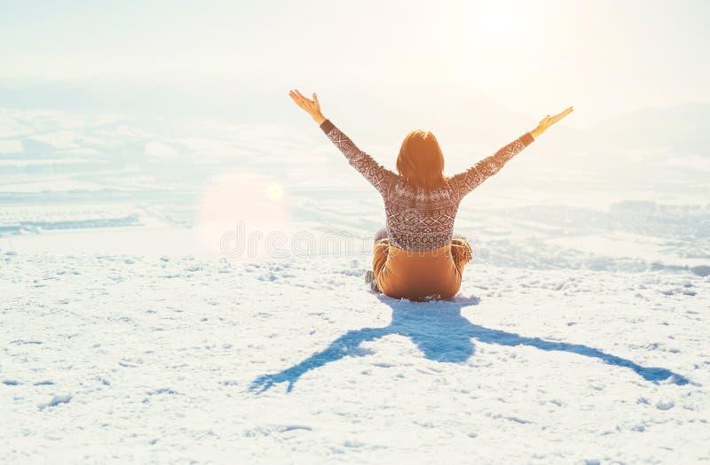 Η ευτυχής γυναίκα κάθεται στο χιονώδη λόφο βουνών πέρα από την πόλη ηλιόλουστος στοκ εικόνες