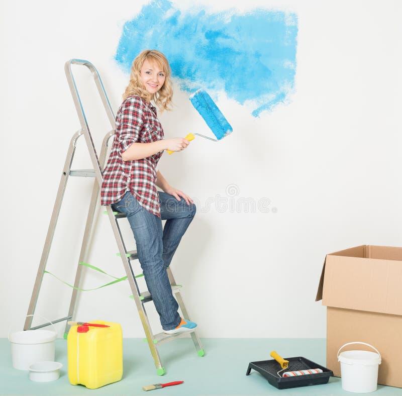 Η ευτυχής γυναίκα κάνει τις επισκευές στο σπίτι στοκ φωτογραφίες