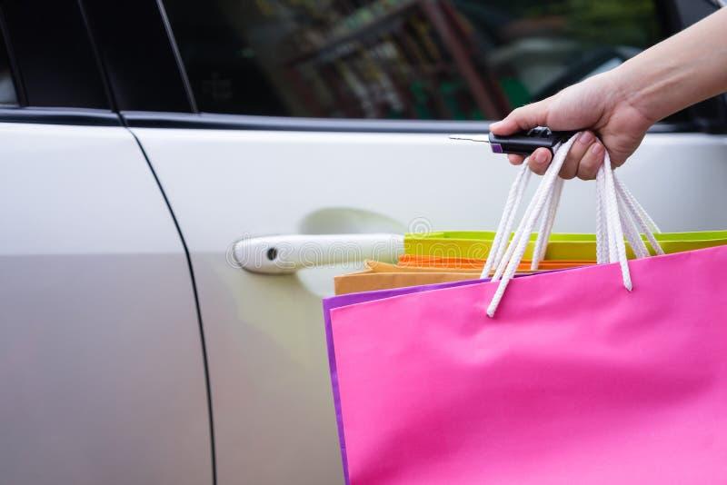 Η ευτυχής γυναίκα με τις αγορές τοποθετεί το αυτοκίνητο ανοίγματος με το χέρι σε σάκκο κρατώντας το μακρινό κλειδί αυτοκινήτων Πι στοκ φωτογραφία