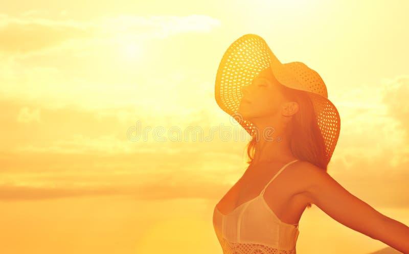 Η ευτυχής γυναίκα ομορφιάς στο καπέλο άνοιξε τα χέρια του, απολαμβάνει το ηλιοβασίλεμα άνω του s στοκ φωτογραφία
