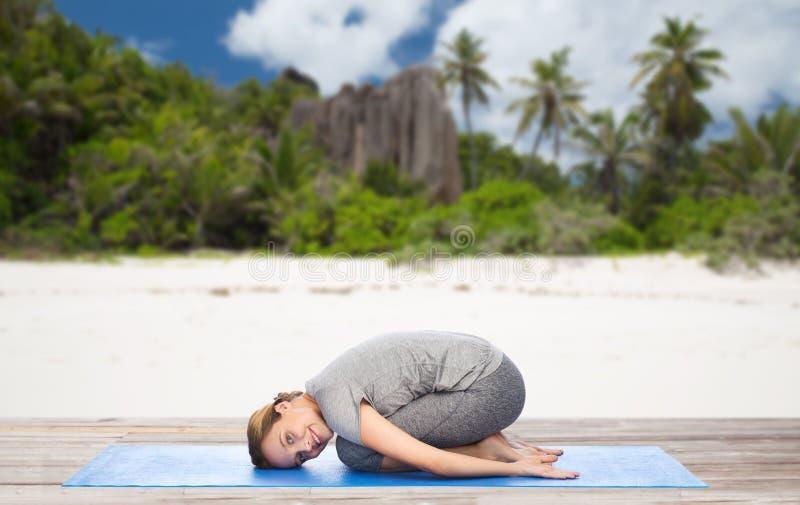 Η ευτυχής γυναίκα που κάνει τη γιόγκα στο παιδί θέτει στην παραλία στοκ εικόνες
