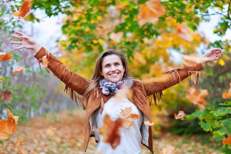 Η ευτυχής γυναίκα ρίχνει τα φύλλα φθινοπώρου στοκ εικόνες