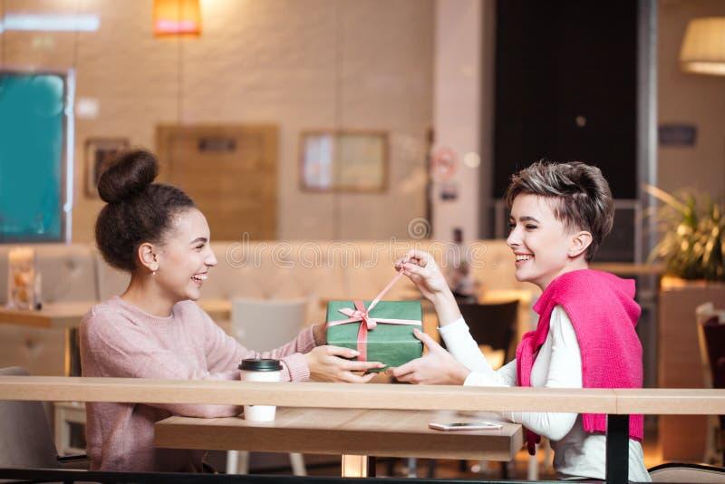 Η ευτυχής γυναίκα συγχαίρει τη φίλη της με το παρόν κιβώτιο καθμένος στον καφέ στοκ εικόνες με δικαίωμα ελεύθερης χρήσης