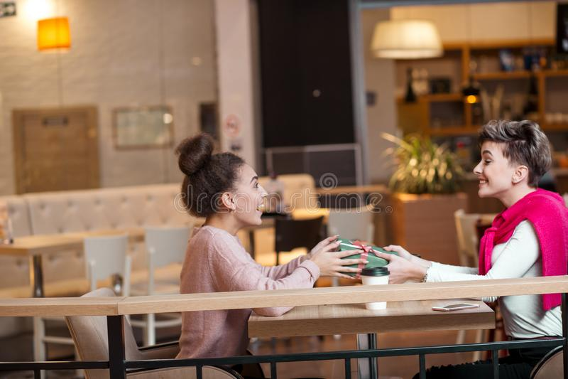 Η ευτυχής γυναίκα συγχαίρει τη φίλη της με το παρόν κιβώτιο καθμένος στον καφέ στοκ εικόνα με δικαίωμα ελεύθερης χρήσης