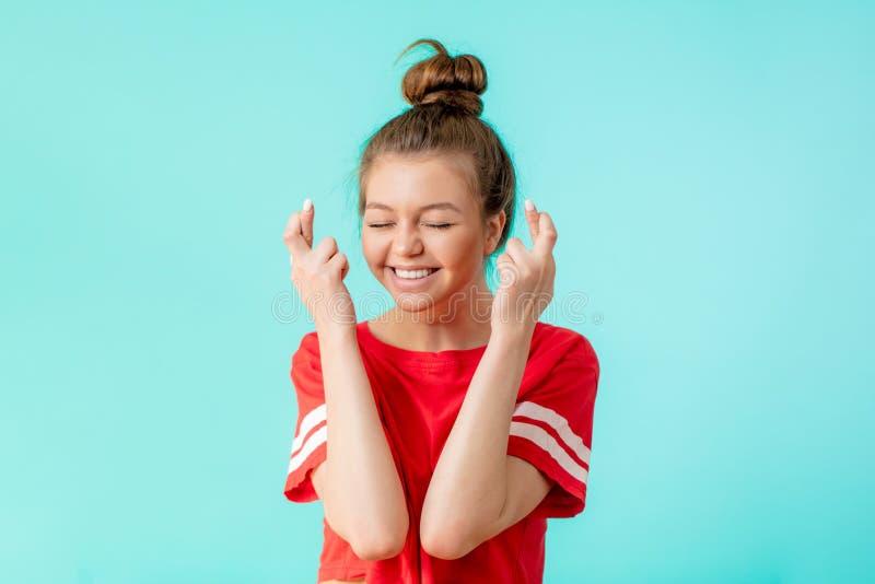 Η ευτυχής ευτυχής γυναίκα φορά την κόκκινη μπλούζα, κρατά τα δάχτυλα διασχισμένα στοκ φωτογραφία