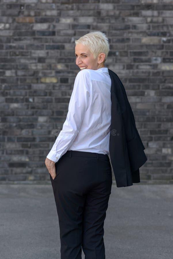 Η ευτυχής γυναίκα φορά το σακάκι της πέρα από τον ώμο της στοκ εικόνα με δικαίωμα ελεύθερης χρήσης