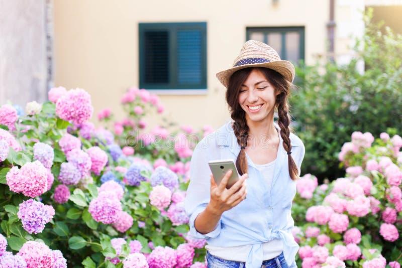 Η ευτυχής γυναίκα χρησιμοποιεί το κινητό τηλέφωνο Κορίτσι με το χαμόγελο στον κήπο χωρών και τους Μπους του hydrangea στοκ εικόνα με δικαίωμα ελεύθερης χρήσης