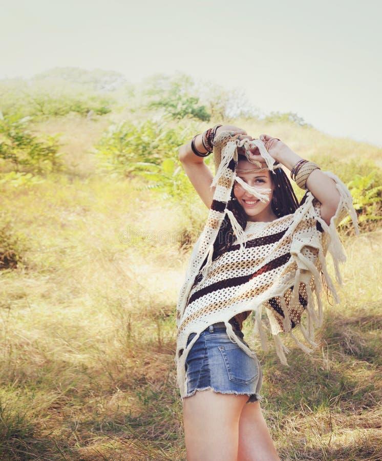 Η ευτυχής γυναίκα ύφους boho έντυσε πλεκτό poncho, τα σορτς τζιν και headband που θέτουν τα χέρια επάνω ενάντια στο ηλιόλουστο πά στοκ εικόνα με δικαίωμα ελεύθερης χρήσης