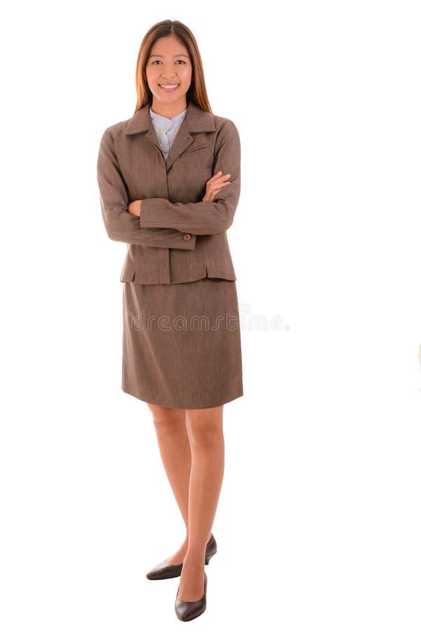 Η ευτυχής επιχειρηματίας στο καφετί κοστούμι χαμογελά και διασχίζει το βραχίονα επάνω στοκ εικόνες