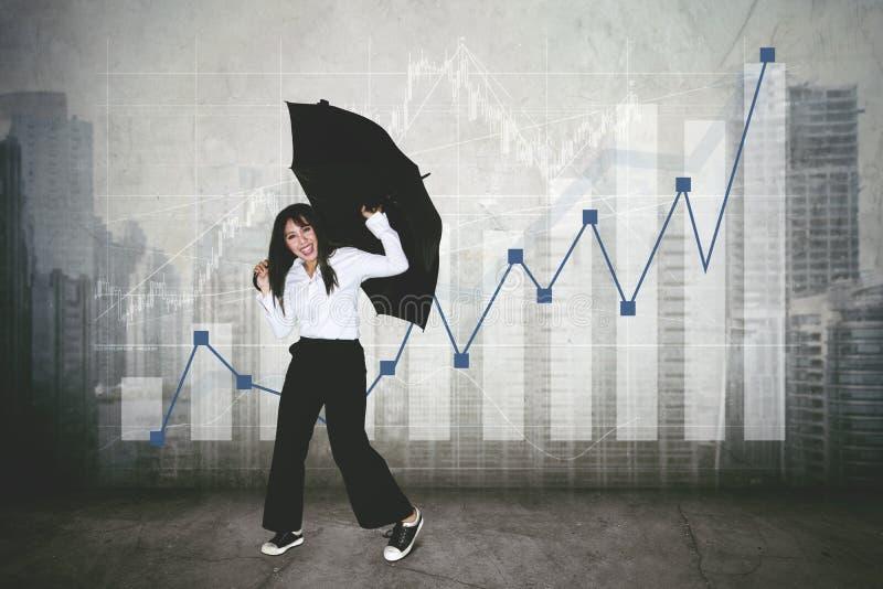 Η ευτυχής επιχειρηματίας χορεύει κοντά στο διάγραμμα αύξησης στοκ φωτογραφία
