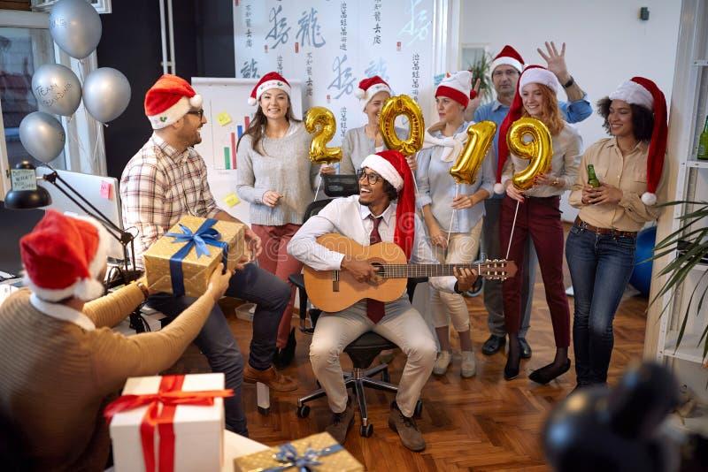 Η ευτυχής επιχειρησιακή ομάδα έχει τη διασκέδαση και το χορό στο καπέλο Santa στο κόμμα Χριστουγέννων στοκ φωτογραφία