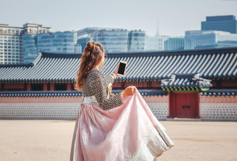 Η ευτυχής Ευρωπαία γυναίκα τουριστών στο εθνικό κορεατικό κοστούμι περπατά μέσω των παλατιών με ένα τηλέφωνο στοκ εικόνες