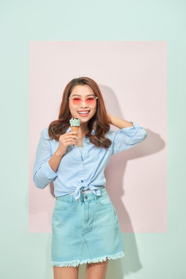 Η ευτυχής ευχάριστη νέα ασιατική γυναίκα με το οδοντωτό χαμόγελο εξετάζει τη κάμερα, κρατά το νόστιμο παγωτό, στέκεται στο ανοικτ στοκ εικόνα με δικαίωμα ελεύθερης χρήσης