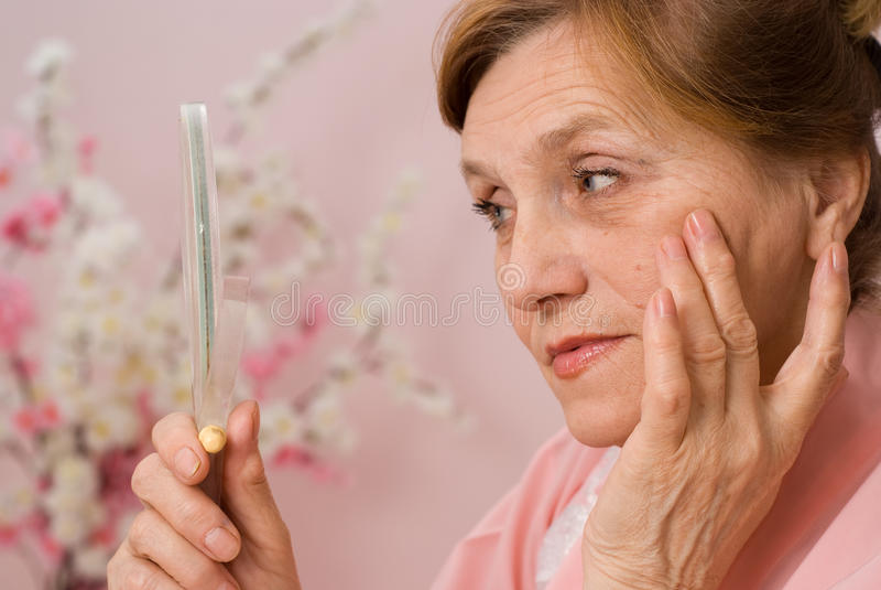 Η ευτυχής ηλικιωμένη γυναίκα κοιτάζει στον καθρέφτη στοκ εικόνες με δικαίωμα ελεύθερης χρήσης